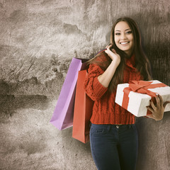 beautiful young woman holding colored shopping bags and gift box