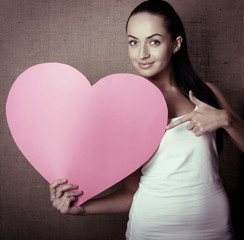 portrait of attractive smiling young woman with pink heart, love