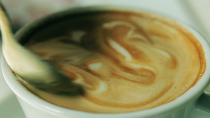 Coffe mixing by a spoon, closeup
