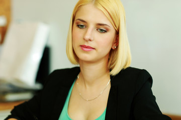 Portrait of a thoughtful blonde businesswoman in office
