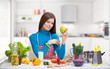 Smiling woman with a green apple in the kitchen