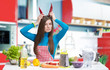 Funny portrait of a young woman with pepper horns in the kitchen