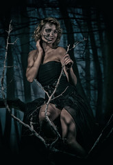 Portrait of a retro woman with skull make-up in the night forest