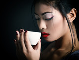 Young beautiful asian woman and tea ceremony, studio shot over b