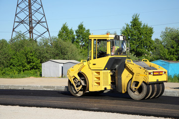 Yellow rolling machinery paving a road