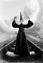 Wizard in black cloak and dunce hat standing on rails