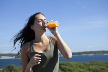 Pretty jogger drinking juice, outdoor portrait