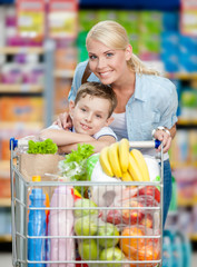 Mother and son with cart full of products in market