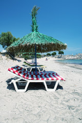 Relaxing sunbeds on the beach under straw umbrella