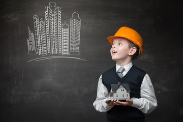 Portrait of boy in hard hat keeping home model
