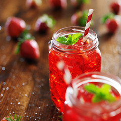 old fashioned jars with vivid red strawberry cocktail