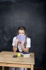 portrait of happy cute student with book in classroom