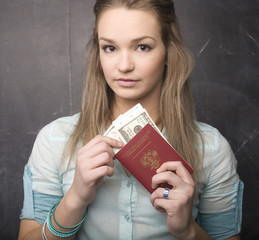 portrait of cute girl student with money and passport
