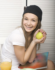 portrait of happy cute girl with breakfast, green apple and