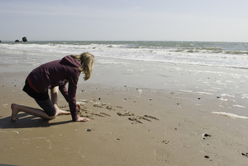 Girl Writing in the Sand on the Beach