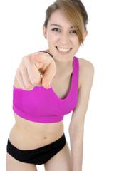 Lachende Frau in Sportbekleidung zeigt