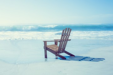 Wooden deck chair in the sand by the sea
