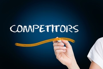 Businesswoman writing the word competitors