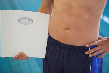 Fit man in swimming trunks standing by the pool holding weighing