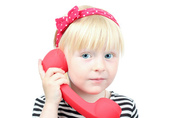 Pretty  little blond girl with a red  retro phone on a white bac