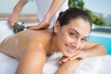 Smiling brunette getting an aromatherapy treatment poolside