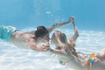 Cute couple kissing underwater in the swimming pool