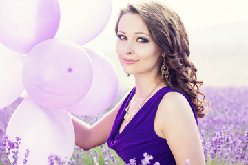 Adorable girl with purple balloons.