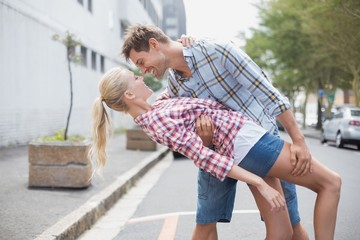 Hip romantic couple dancing in the street