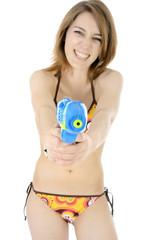 Frau in Bikini schießt mit Spritzpistole