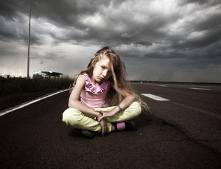 Sad child near road