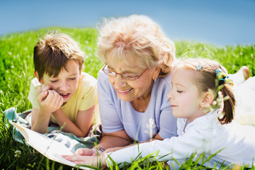 grandmother reading book to grandchildren