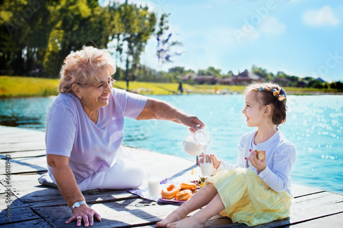 Deurstickers Picknick Grandmother with granddaughter eating breakfast