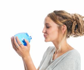 Mädchen küsst blaues Sparschwein