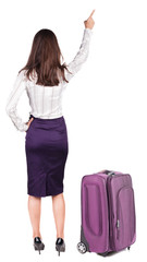 Back view of young brunette woman traveling with suitcas and poi