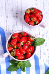 Ripe sweet strawberries in pot and mug