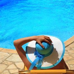 Woman in hat by the pool