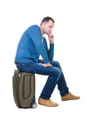 back view of a man sitting on a suitcase.