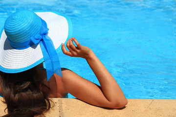Woman in hat with turquoise water in background