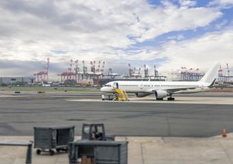 White passenger airplane,service equipment, parked on runway