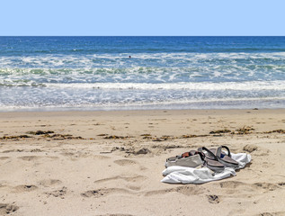 Flip flops in sand.Ocean waves background.Relaxing,leisure idea.