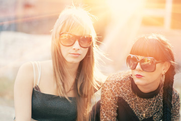 Two female in sunglasses backlit by sunset