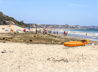 Bright orange kayak on beach.People relaxing,blurred background.