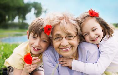 happy grandmother with grandchildren outdoors