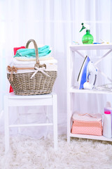 Colorful towels in basket on chair, on home interior background