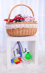 Colorful clothes in basket on chair, on light background
