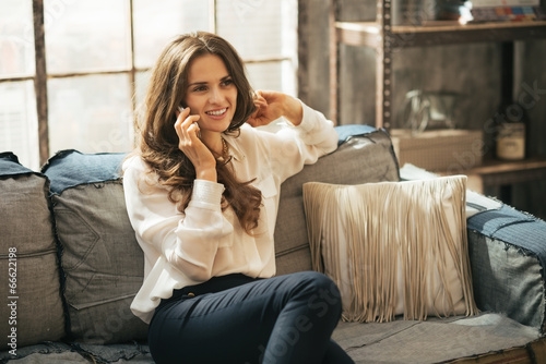Leinwanddruck Bild Happy young woman talking cell phone in loft apartment