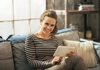 Smiling young woman sitting on sofa and using tablet pc