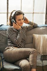 Happy young woman sitting on couch and listening music