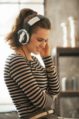 Portrait of happy young woman listening music in headphones