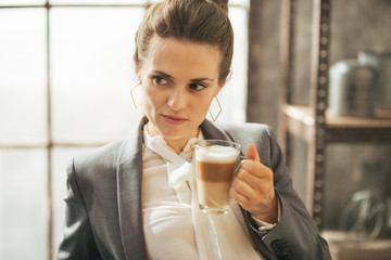 Portrait of thoughtful business woman drinking coffee latte